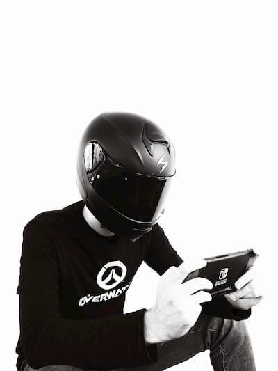 Sanne Maarten Veenstra met een motorhelm op zijn hoofd en een Nintendo Switch in zijn handen