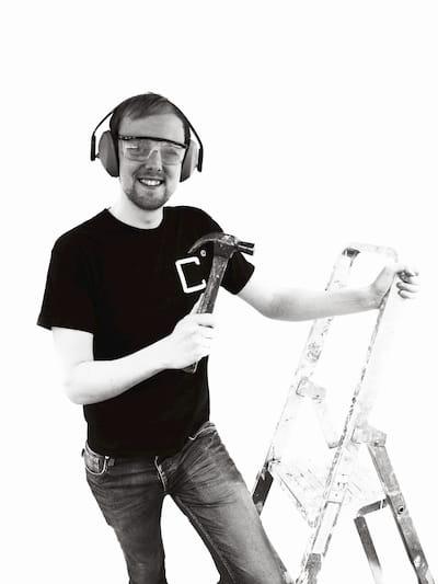 Menno Commandeur met een hamer op een ladder